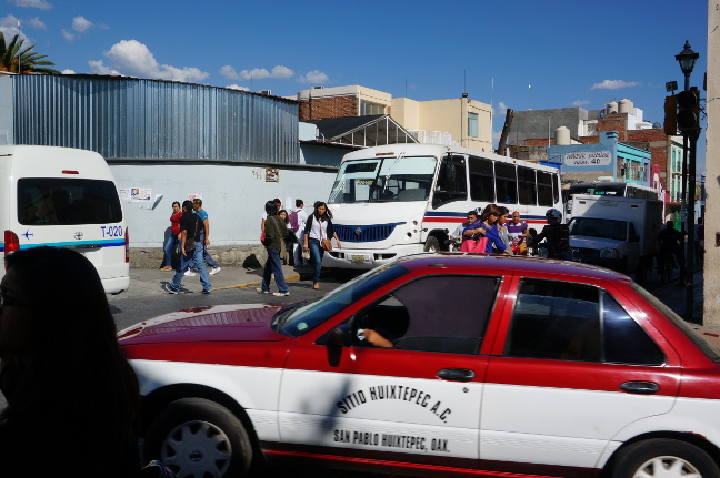 Dueling for passengers, an urban bus and a collectivo in Oaxaca, Mexico.